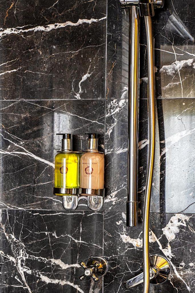 pump up bottles in shower with black tiles